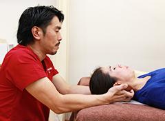首の施術を行う男性の写真